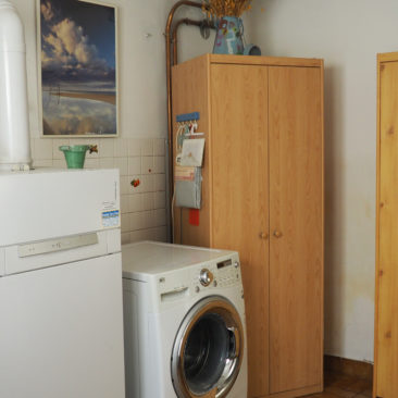 Laundry with washing machine and central heating unit